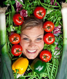 Cute blond girl shot in studio with vegetables aroound the head Stock Photo