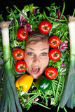 Cute blond girl shot in studio with vegetables aroound the head Stock Images