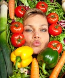 Cute blond girl shot in studio with vegetables aroound the head Royalty Free Stock Photography