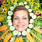 Cute blond girl shot in studio with vegetables aroound the head Royalty Free Stock Photos