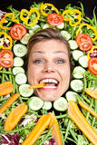 Cute blond girl shot in studio with vegetables aroound the head Stock Image