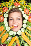 Cute blond girl shot in studio with vegetables aroound the head Stock Photography