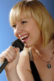 Cute blond girl singing. With microphone on stage royalty free stock image