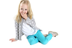 Cute blond girl sitting hand to mouth laughing Stock Image