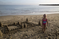 Cute blond girl standing by her sand castle smiling Stock Image