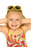 Cute blond girl wearing swimsuit hands over her ears. Cute blond blue eyed Caucasian girl wearing swimsuit smiling at the camera with her hands over ears and stock image