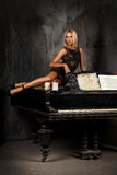 Cute blond hair woman lying on piano and looking away Stock Photos