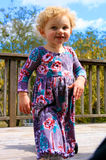 Cute Blond Haired Little Girl. A cute little girl walks with an interesting posture and looks at the camera Royalty Free Stock Photos