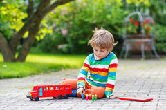 Cute blond kid boy playing with red school bus and toys Royalty Free Stock Photo