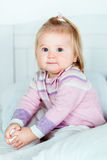Cute blond little girl with big grey eyes and plump cheeks Royalty Free Stock Photography