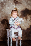 Cute blond little girl sitting on white chair Stock Image
