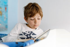 Cute blond little kid boy in pajamas reading book in his bedroom Royalty Free Stock Image