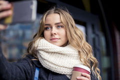 Cute blond with long hair in the street makes Selfe Stock Photos