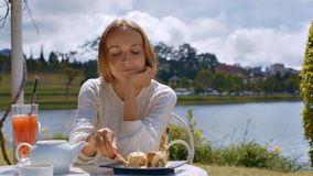 Woman Eats Ice Cream with Sweet Tube at Cafe Table. Cute blond long haired woman in white sweater eats ice cream with sweet tube in cafe against pictorial river stock video