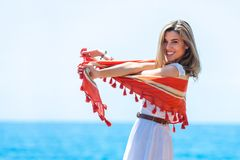 Cute blond playing with red scarf outdoors. Stock Photography