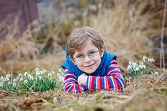 Cute blond preschool kid boy discovering first spring flowers, beautiful snowdrops Royalty Free Stock Image