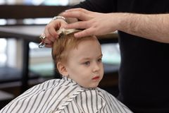 Cute blond serious baby boy with blue eyes in a barber shop having haircut by hairdresser. Children`s fashion. Indoors, dark background, copy space stock images