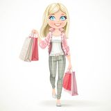 Cute blond shopaholic girl goes with paper bags Stock Images