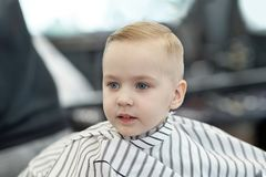 Cute blond smiling baby boy with blue eyes in a barber shop after haircut by hairdresser. Children fashion in salon. Indoors, dark background, copy space royalty free stock images