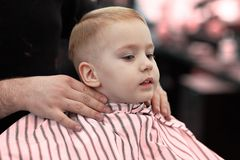 Cute blond smiling baby boy with blue eyes in a barber shop having haircut by hairdresser. Hands of stylist. Children fashion. stock images
