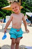 Cute blond smiling  child at the beach. Cute blond little  smiling boy  playing with the sand at the beach Royalty Free Stock Photos