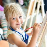 Cute blond smiling girl painting on easel in workshop lesson at art studio. Kid holding brush in hand and having fun drawing with. Paints. Child development stock photography