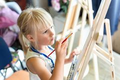 Cute blond smiling girl painting on easel in workshop lesson at art studio. Kid holding brush in hand and having fun drawing with. Paints. Child development stock images