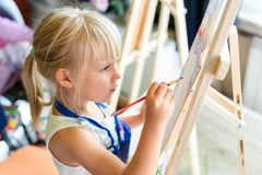 Cute blond smiling girl painting on easel in workshop lesson at art studio. Kid holding brush in hand and having fun. Drawing with paints. Child development royalty free stock photo