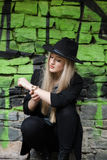Cute blond teen against stone wall with green graffiti Stock Image