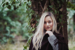 Cute blond teen lean against a tree covered with green leaves stock photography
