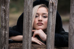 Cute blond teen with nice figures standing behind wooden fence royalty free stock images