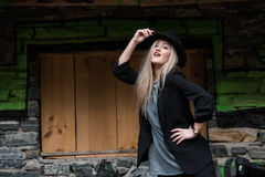 Cute blond teen wear black jacket and hat. Cute blond teen with long straight hair wear black jacket and hat standing against stone wall with big window stock images