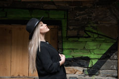 Cute blond teen wear black jacket and hat. Cute blond teen with long straight hair wear black jacket and hat standing against stone wall with big window royalty free stock photography