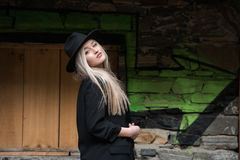 Cute blond teen wear black jacket and hat. Cute blond teen with long straight hair wear black jacket and hat standing against stone wall with big window royalty free stock image
