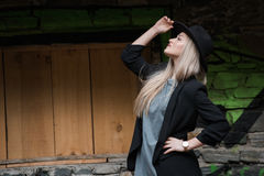 Cute blond teen wear black jacket and hat. Cute blond teen with long straight hair wear black jacket and hat standing against stone wall with big window royalty free stock images