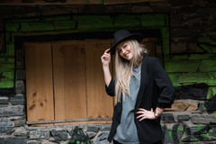 Cute blond teen wear black jacket and hat. Cute blond teen with long straight hair wear black jacket and hat standing against stone wall with big window stock photos