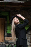Cute blond teen wear black jacket and hat. Cute blond teen with long straight hair wear black jacket and hat standing against stone wall with big window royalty free stock photo