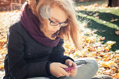 Cute blond teenage girl usin smartphone Stock Photos