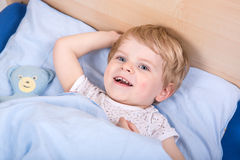 Cute blond toddler boy in bed Royalty Free Stock Images
