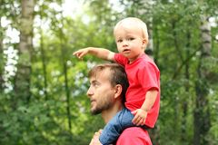 Cute blond toddler boy sits on his fathers`s shoulders and pointing by finger. Childhood concept. Lifestyle.  stock images