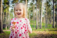 Cute toddler girl picking mushrooms in a forest. Happy child holding a mushroom and laughing stock photography
