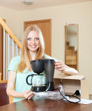 Cute blond unpacking and reading manual for new coffeemaker at h Royalty Free Stock Images