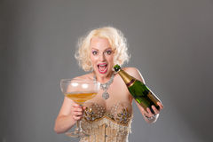 Cute blond woman celebrates with huge glass of champagne = grey Royalty Free Stock Images