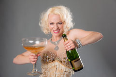 Cute blond woman celebrates with huge glass of champagne = grey Stock Image