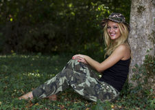 Cute blond woman dressed in camouflage in forest Stock Image
