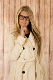 Cute blond woman holding chin wearing glasses and white coat Stock Photo