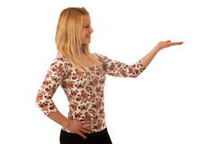 Cute blond woman pointing into copy space as she is showing a pr. Oduct for commercial Royalty Free Stock Photos