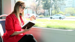 Cute blond woman reading book while riding tram stock video