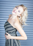 Cute blond woman with steel door. Beautiful tall thin laughing woman Stock Images