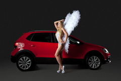 Cute blonde in angel costume standing near red car Royalty Free Stock Photo